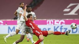 Gelandang Bayern Munich, Leon Goretzka (kanan) menguasai bola dibayangi bek Bayer Leverkusen, Edmond Tapsoba dalam laga lanjutan Liga Jerman 2020/2021 pekan ke-30 di Allianz Arena, Munich, Selasa (20/4/2021). Bayern Munich menang 2-0 atas Leverkusen. (AP/Matthias Schrader/Pool)