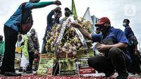 Massa buruh menaburkan bunga sebagai simbol duka atas kebijakan pemerintah di kawasan Patung Kuda, Jakarta, Senin (2/11/2020). Buruh dari berbagai serikat pekerja menggelar demo terkait penolakan pengesahan omnibus law Undang-Undang Cipta Kerja dan upah minimum 2021. (merdeka.com/Iqbal S Nugroho)