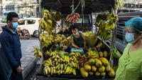 Seorang pria menjual pisang dari truk di sebuah pasar sehari setelah militer Myanmar merebut kekuasaan, Yangon, Myanmar, Selasa (2/2/2021). Militer Myanmar menahan pemimpin yang terpilih secara demokratis Aung San Suu Kyi dan memberlakukan keadaan darurat satu tahun. (STR/AFP)