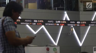 Pengunjung melintas dekat layar monitor pergerakan saham di gedung Bursa Efek Indonesia, Jakarta, Rabu (2/1). Indeks Harga Saham Gabungan (IHSG) pada pembukaan perdagangan saham 2019 menguat 10,4 poin atau 0,16% ke 6.204. (Liputan6.com/Angga Yuniar)