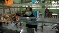 Sejumlah guru membersihkan kelas yang akan digunakan di SDN Kenari 08, Jakarta, Selasa (6/4/2021). Pemerintah Provinsi DKI Jakarta akan melakukan uji coba pembelajaran tatap muka terbatas di 100 sekolah mulai 7 April hingga 29 April 2021. (Liputan6.com/Faizal Fanani)