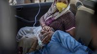 Seorang pasien bernapas dengan bantuan oksigen yang disediakan oleh tempat ibadah Gurdwara, Sikh, di dalam sebuah mobil di New Delhi pada 24 April 2021. India mengalami kekurangan oksigen yang kritis di tengah badai infeksi Covid-19 yang menghancurkan sistem kesehatannya. (AP Photo/Altaf Qadri)