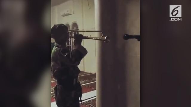 Seorang kakek punya cara unik membangunkan orang sahur dengan trompet kenegaraan.