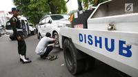 Petugas Dinas Perhubungan mengaitkan kendaraan pada mobil derek di kawasan Pasar Baru, Jakarta, Kamis (14/12). Parkir sembarang di pinggir jalan ini membuat kesemrawutan dan menimbulkan kemacetan. (Liputan6.com/Immanuel Antonius)