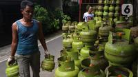 Pekerja membawa tabung gas LPG 3 kilogram (kg) di Jakarta, Rabu (16/12/2020). Kenaikan gas elpiji 3 kg pada 2021 tersebut dengan mempertimbangkan kebutuhan gas yang terus meningkat terutama di masa pandemi Virus Corona. (Liputan6.com/Angga Yuniar)