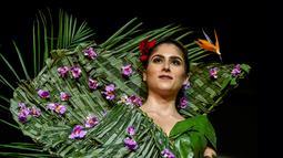 Model mengenakan busana rancangan desainer Kolombia, Estefania Russi selama BioFashion Show di Cali  pada 17 November 2018. Busana-busana yang ditampilkan di ajang ini seluruhnya terbuat dari tanaman hidup, bunga dan unsur organik lain. (Luis ROBAYO/AFP)