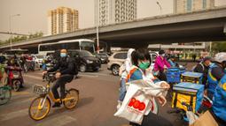 Seorang wanita yang mengenakan masker wajah menunggu untuk menyeberangi persimpangan saat badai pasir di Beijing, China, Kamis (6/5/2021). Debu dan badai pasir akhir musim semi mengirim indeks kualitas udara melonjak di Ibu Kota China pada hari ini. (AP Photo/Mark Schiefelbein)