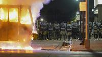 Polisi berdiri dekat truk sampah yang terbakar saat protes di Kenosha, Wisconsin, Amerika Serikat, Senin (24/8/2020). Protes dipicu oleh penembakan Jacob Blake oleh petugas polisi Kenosha sehari sebelumnya. (AP Photo/Morry Gash)