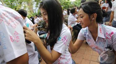 Sejumlah siswa-siswi SMA 6 melampiaskan kegembiraannya dengan aksi corat-coret seragamnya (Liputan6.com/Faizal Fanani)