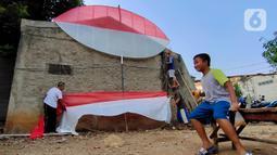 Seorang anak terlihat saat warga membuat layang-layang merah putih setinggi enam meter di Kawasan Peninggilan, Tangerang, Senin (10/8/2020). Layang-layang merah putih tersebut dibuat untuk memeriahkan HUT Ke-75 Kemerdekaan Republik Indonesia. (Liputan6.com/Angga Yuniar)