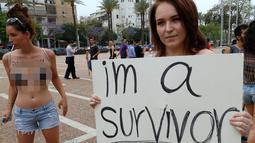 Dua wanita berunjuk rasa di pantai Mediterania Israel Tel Aviv (4/5). Protes ini terinspirasi kelompok wanita Kanada yang meluncurkan protes tahun 2011 sebagai tanggapan atas pertanyaan bahwa mereka ingin menghindari pelecehan. (AFP Photo/Jack Guez)