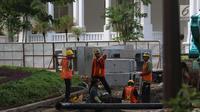 Sejumlah pekerja menyelesaikan perbaikan drainase Kompleks Istana Kepresidenan, Jakarta, Senin (18/12). Pengerjaan rehabilitasi drainase kawasan istana kepresidenan tersebut guna mengantisipasi ancaman banjir. (Liputan6.com/Angga Yuniar)