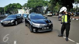 Petugas memeriksa pelat nomor sebuah mobil yang melintas pada tanggal ganjil di Bundaran Senayan, Jakarta, Rabu (31/8). Sejak kemarin petugas mulai memberlakukan sanksi  kepada pengendara yang melanggar aturan ganjil-genap. (Liputan6.com/Gempur M Surya)