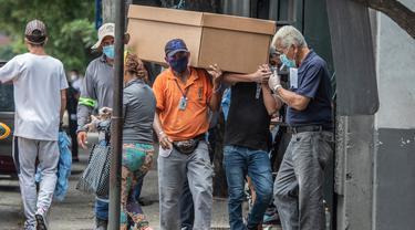 Pekerja makam membawa jenazah dalam peti mati kardus untuk dimakamkan di Pemakaman Umum di Guayaquil, Ekuador, Senin (6/4/2020). Kehabisan peti mati, kota terbesar di Ekuador yang menjadi klaster wabah virus corona itu terpaksa menggunakan kotak kardus untuk korban Covid-19. (AP/Luis Perez)