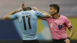 Bek timnas Uruguay, Matias Vina menutupi kepalanya setelah gagal melakukan tendangan penalti dalam laga perempat final Copa America 2021 di Stadion Nacional de Brasilia, Brasil, Minggu (4/7/2021) pagi WIB. Kolombia mengalahkan Uruguay lewat adu penalti dengan skor 4-2. (AP Photo/Silvia Izquierdo)