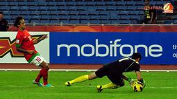 Pemain depan Timnas Indonesia, Irfan Bachdim berhadapan dengan kiper Laos Sengphachan Bounthisanh dalam laga Piala AFF Suzuki 2012, di Stadion Bukit Jalil, Kuala Lumpur, Malaysia. Kamis, 25/11/2012. Pertandingan Berakhir seri 2-2.