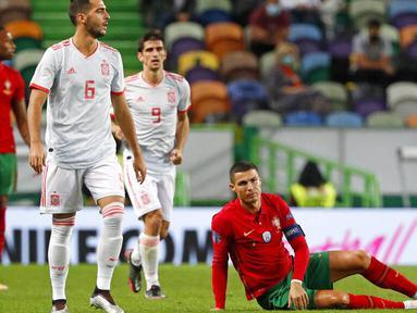 Striker Portugal, Cristiano Ronaldo, terduduk lesu di lapangan saat melawan Spanyol pada laga uji coba di Stadion Jose Alvalede, Kamis (8/10/2020). Kedua tim bermain imbang 0-0. (AP Photo/Armando Franca)