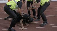 Suporter Timnas Indonesia diamankan petugas pengamanan ketika akan menghampiri suporter Malaysia saat laga Kualifikasi Piala Dunia 2022 di SUGBK, Jakarta, Kamis (5/9). (Bola.com/Peksi Cahyo)