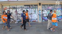 Sejumlah tersangka digiring petugas usai rekonstruksi pembunuhan anak punk di perempatan Gaplek, Pamulang, Rabu (6/2). MR dibunuh secara kejam dengan cara ditusuk dan telinga serta kelingkingnya dipotong oleh para tersangka. (Merdeka.com/Arie Basuki)