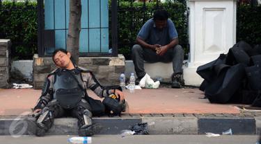 Seorang polisi tertidur di pinggir Jalan Merdeka Barat, Jakarta, Jumat (4/11). Ribuan aparat gabungan berjaga saat massa melakukan aksi di depan Istana Negara menuntut penegakan hukum kasus dugaan penistaan agama. (Liputan6.com/Helmi Fithriansyah)