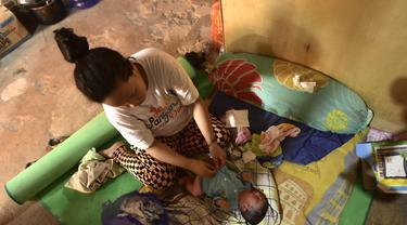 Armila merawat bayi laki-lakinya yang berusia sehari, Muhammad Al Aksa, di tempat pengungsian sementara setelah gempa berkekuatan 6,2 skala Richter mengguncang kota Mamuju, Sulawesi, Selasa (19/1/2021). (AFP/Firdaus)