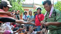 Petugas Vihara Dharma Bakti membagikan angpao dari umat Tionghoa yang datang untuk sembahyang jelang perayaan Imlek, Jakarta, (7/2/2016). Jelang Imlek, ratusan pengemis penuhi Vihara Dharma Bhakti untuk mendapatkan angpao. (Liputan6.com/Yoppy Renato)