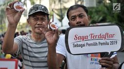 Warga menunjukan pin anti golput usai melakukan pendaftaran daftar pemilih tetap (DPT) di kawasan Car Free Day, Jakarta, Minggu (21/10). Pos pendaftaran ini bertujuan mendata warga yang belum terdaftar dalam DPT Pemilu 2019. (Merdeka.com/Iqbal S. Nugroho)