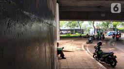 Pengemudi ojek online beristirahat di jalur putar balik Jalan Gatot Soebroto, Kuningan, Jakarta, Selasa (12/11/2019). Jalur yang kini hanya bisa dilalui kendaraan roda dua itu menjadi lokasi sebagian pemotor beristirahat karena teduh tertutup jalan tol dalam kota. (Liputan6.com/Immanuel Antonius)