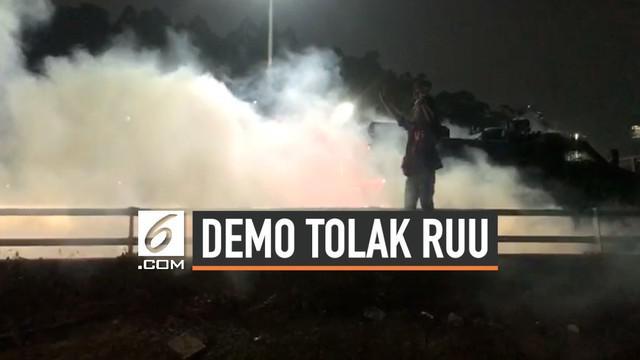 Polisi menembakkan gas air mata dan menyemprotkan air menggunakan water cannon ke arah mahasiswa saat demonstrasi menolak pengesahan RUU KUHP dan revisi UU KPK di depan Gedung DPR.
