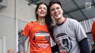 Pasangan Baim Wong dan Paula Verhoeven tersenyum saat mengenakan kaus dukungan untuk aktor Tio Pakusadewo di Pengadilan Negeri Jakarta Selatan, Jalan Ampera Raya, Jakarta, Kamis (28/6). (Liputan6.com/Faizal Fanani)