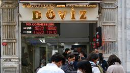 Orang-orang menunggu di luar agen penukaran mata uang dekat alun-alun Taksim ketika lira Turki terperosok ke level terendah sepanjang sejarah di Istanbul, Senin (25/10/2021). Lira melemah imbas pengusiran duta besar AS dan sembilan negara Barat lainnya oleh Presiden Tayyip Erdogan. (Ozan KOSE/AFP)