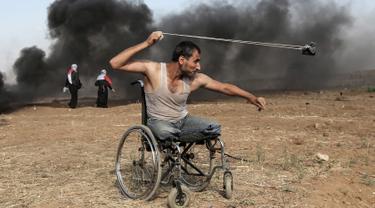 Seorang pria Palestina bernama Saber al-Ashkar melemparkan batu dari kursi rodanya saat terlibat bentrokan dengan pasukan Israel di jalur Gaza (11/5). Sejauh ini lebih dari 50 warga Palestina tewas oleh tembakan tentara Israel. (AFP/Mahmud Hams)