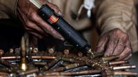 Abu Ali al-Bitar mengelem bekas peluru untuk menciptakan karya seni di Damaskus, Suriah (20/4). Sejak Suriah menjadi negara konflik, Abu Ali mengumpulkan sisa amunisi dan peluru bekas untuk dijadikan karya seni. (AFP/Sameer Al-Doumy)