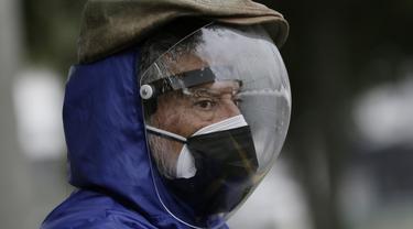 Seorang pria yang mengenakan pelindung wajah penuh dan masker ganda  menunggu gilirannya divaksinasi Covid-19 di luar pusat vaksinasi Social Security Institute di Quito, Ekuador, Kamis (6/5/2021). Para lansia dan pendampingnya menunggu berjam-jam untuk divaksinasi. (AP Photo/Dolores Ochoa)