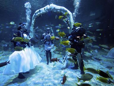 Lisa Huggins dan Chris Jackson selama upacara pernikahan bawah air mereka di Bear Grylls Adventure, di Birmingham, Inggris, Rabu (8/9/2021). Penggemar menyelam itu berencana akan menikah di luar negeri tetapi gagal akibat Covid-19, dan mencari alternatif yang unik. (Jacob King/PA via AP)