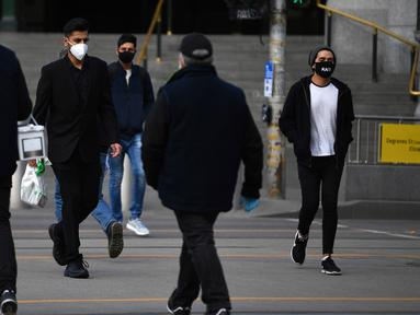 Orang-orang yang memakai masker berjalan di luar Stasiun Flinders Street di Melbourne, Kamis (23/7/2020). Sebagian penduduk kota terpadat kedua di Australia, Melbourne, mematuhi undang-undang baru yang mewajibkan pemakaian masker. (James Ross / AAP Image via AP)