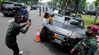Warga memotret anak di kendaraan taktis TNI yang dipamerkan di depan Istana Merdeka, Jakarta, Senin (4/10/2021). Ratusan alat utama sistem persenjataan (Alutsista) TNI dipamerkan sepanjang pinggir jalan sekeliling kawasan Monas dalam rangka peringatan HUT ke-76 TNI. (merdeka.com/Arie Basuki)