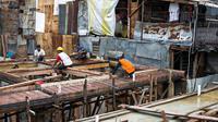 Para pekerja menyelesaikan pembangunan rumah panggung di dekat bantaran Kali Ciliwung, Kampung Melayu, Jakarta, Rabu (7/4/2021). Pemerintah Provinsi DKI Jakarta melakukan renovasi terhadap 40 hunian warga Kampung Melayu menjadi rumah panggung. (Liputan6.c