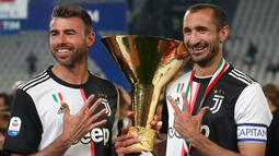 Bek Juventus, Andrea Barzagli dan Giorgio Chiellini berpose dengan Piala Liga Italia Serie A di Stadion Allianz, Turin (19/5/2019). Juventus meraih gelar scudetto kedelapan secara beruntun sekaligus rekor baru. (AP Photo/Antonio Calanni)