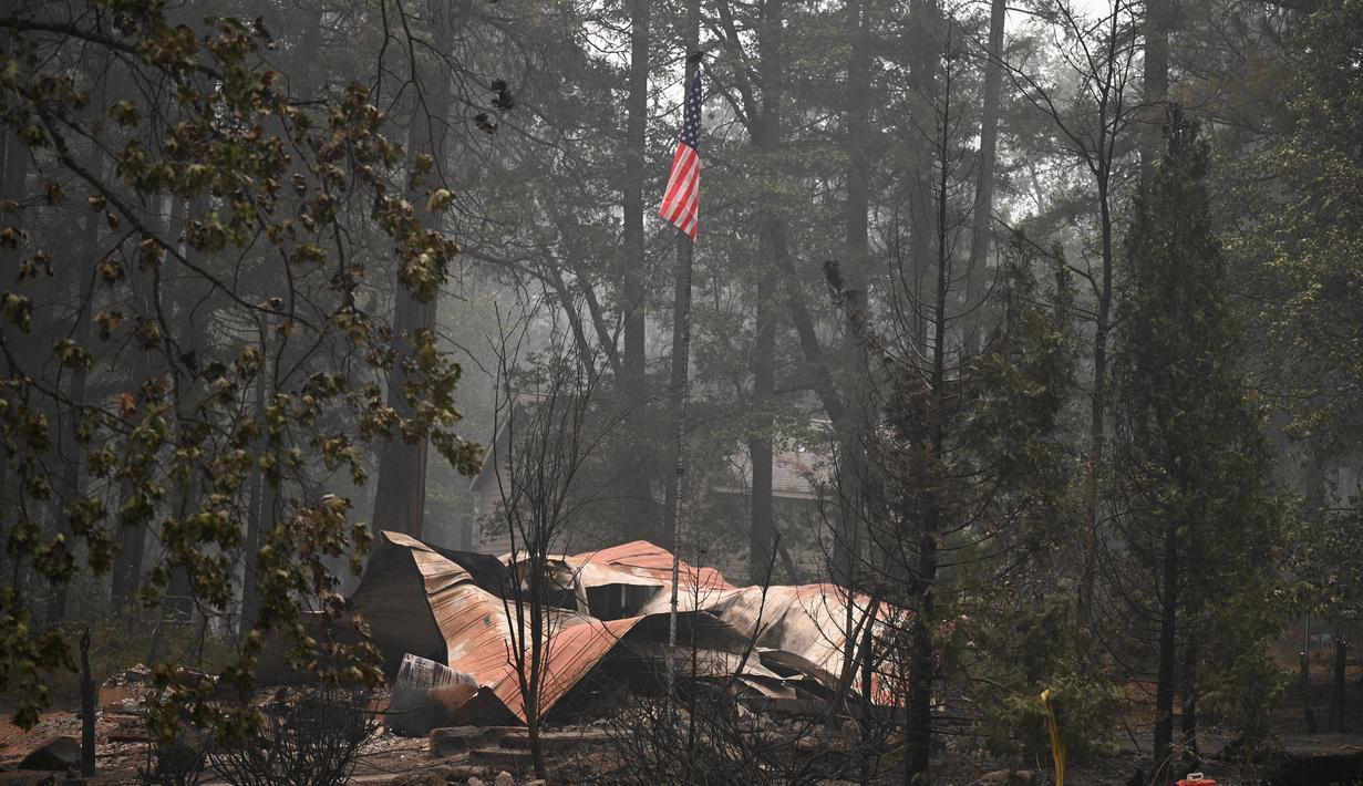 Sebuah bendera Amerika terlihat di atas properti yang terbakar dalam Kebakaran Dixie Fire di daerah Air Terjun India di Plumas County, California (26/7/2021). Api menghanguskan beberapa tempat tinggal di daerah tersebut. (AFP/Robyn Beck)
