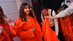 Pengunjung diberikan baju tahanan saat tiba di bar koktail Alcotraz, London , 11 Oktober 2018. Bar berkonsep penjara ini terinspirasi dari karya fiksi terkenal, Shawshank Redemption dan serial Netflix bertajuk 'Orange Is a New Black'. (BEN STANSALL / AFP)