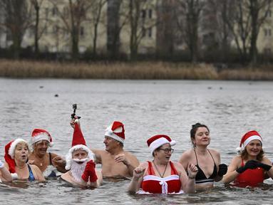 """Anggota klub renang """"Berliner Seehunde"""" (Berlin Seals) berendam di Danau Orankesee, Berlin, Minggu (25/12). Kegiatan yang sudah menjadi tradisi ini merupakan bagian dari perayaan tradisional Natal bagi warga Berlin. (Tobias SCHWARZ / AFP)"""
