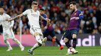 Gelandang Real Madrid, Toni Kroos berusaha merebut bola yang dibawa Striker Barcelona, Lionel Messi selama pertandingan lanjutan La Liga Spanyol di Santiago Bernabeu, Madrid (2/3). Barcelona menang tipis atas Real Madrid 1-0. (AP Photo/Andrea Comas)