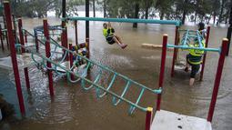Orang-orang bermain dengan peralatan di taman bermain di tepi Sungai Nepean di Jamisontown di pinggiran barat Sydney (22/3/2021). Banjir membuat  ribuan orang mengungsi dari rumah mereka karena hujan masih melanda wilayah tersebut. (AP Photo/Mark Baker)