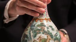 Sebuah vas China antik yang diyakini berasal dari masa Dinasti Qing pada abad ke-18 diperlihatkan di rumah lelang Sotheby, Paris, Selasa (22/5). Vas tersebut lama tersimpan di dalam sebuah kotak sepatu milik satu keluarga di Perancis. (AFP/Thomas SAMSON)