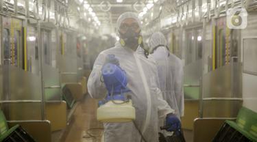Petugas mengenakan pakaian pelindung menyemprotkan disinfektan bagian dalam pada rangkaian KRL Jabodetabek di Dipo Depok, Jawa Barat, Jumat (13/3/2020). Pembersihan bagian luar dan bagian dalam kereta menggunakan cairan disinfektan guna mengantisipasi penyebaran virus corona (Covid-19). (Liputan6.co
