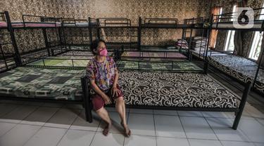 Tri duduk di antara ranjang kasur yang lama tak dihuni di yayasan penyalur asisten rumah tangga Mekar Jaya, Jakarta, Selasa (11/5/2021). Pandemi Covid-19 yang berkepanjangan menyebabkan jasa penyalur Infal yang biasa ramai di kala menjelang Lebaran kini mendadak sepi. (merdeka.com/Iqbal S Nugroho)
