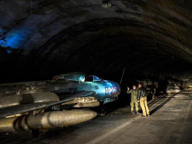 Tentara Albania berjalan di sebelah pesawat tempur MIG-19 dalam terowongan utama Pangkalan Udara Gjader di dekat Kota Lezhe, 5 Februari 2019. Pangkalan Udara Gjader berlokasi dalam perut gunung tandus. (Gent Shkullaku/AFP)
