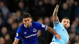 Bek Manchester City, Nicolas Otamendi berebut bola dengan pemain Everton, Dominic Calvert-Lewin selama pertandingan lanjutan Liga Inggris di Goodison Park Stadium (6/2). Hasil ini membuat City memuncaki klasemen Liga Inggris. (Peter Byrne/PA via AP)