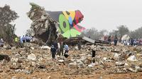 Polisi dan pekerja penyelamat berdiri di antara sisa-sisa Al Afriqiyah Flight 8U771 yang hancur (AP)